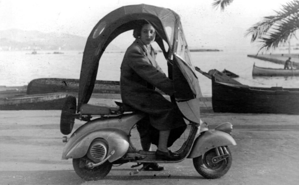 Una donna alla guida di una Vespa con parabrezza e parapioggia, 1948