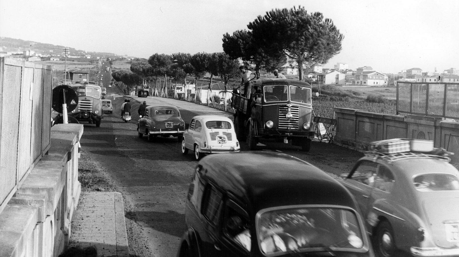 """Lazio, strada statale 7 """"Via Appia"""", automobili in transito durante i lavori per l'ampliamento della carreggiata nei pressi di Roma, 1959 (Archivio storico Anas)"""